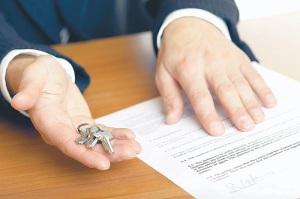 Мужчина держит ключи от квартиры в руке, чтобы передать их жене