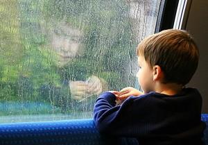 Ребенок смотрит окно, ждет когда его усыновят